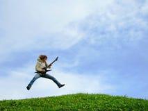 Junger Musiker springt mit Gitarre stockfotografie