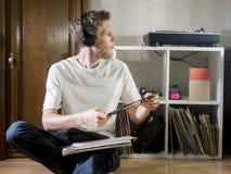 Junger Musikfreundmann, in zufälligem und in den Kopfhörern mit Vinylaufzeichnungen zu Hause in sitzen stockfotografie