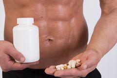 Junger muskulöser Kerl Trägt Nahrung zur Schau Nach der Ausbildung nimmt Tabletten an stockfotografie