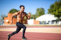 Junger muskulöser Mann bereit, ein Bahntreffen zu beginnen Stockfotografie