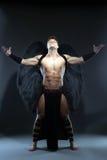 Junger muskulöser Mann, der aufwirft als gefallener Engel Lizenzfreies Stockfoto