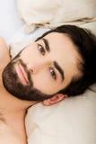 Junger muskulöser Mann, der im Bett liegt Lizenzfreie Stockfotografie