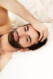 Junger muskulöser Mann, der im Bett liegt Lizenzfreie Stockbilder