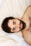 Junger muskulöser Mann, der im Bett liegt Stockfoto