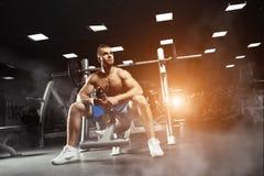 Junger muskulöser Mann, der mit einer Flasche Wasser in der Turnhalle sitzt Lizenzfreie Stockbilder