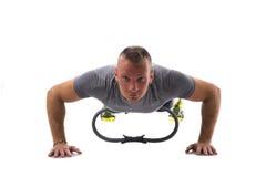 Junger muskulöser Mann, der mit Pilates-Ring lokalisiert auf Weiß trainiert Lizenzfreie Stockfotos