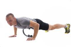 Junger muskulöser Mann, der mit Pilates-Ring lokalisiert auf Weiß trainiert Stockfotos