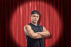 Junger muskulöser Mann in der schwarzen Sportkleidung auf rotem Hauptvorhanghintergrund lizenzfreies stockfoto