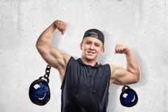 Junger muskulöser Mann in der schwarzen Sportkleidung, die Bizeps mit Karikatur zeigt, kettete die Bälle an, die auf weißen Hinte lizenzfreie stockfotos