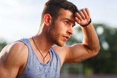 Junger muskulöser verschwitzter Mann nach Training draußen am sonnigen Tag Lizenzfreies Stockfoto