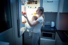 Junger Mutter- und Babysohn, der innerhalb des Kühlschranks nach somethin sucht Stockbilder