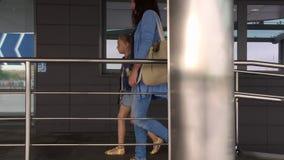 Junger Mutter- und Tochterjugendlicher mit dem Koffer, der zum Flughafenabfertigungsgebäude kommt stock footage