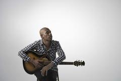 Junger nachdenklicher Mann mit Gitarre Stockfoto