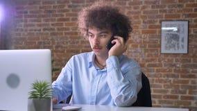 Junger nerdy Geschäftsmann mit dem gelockten Haar und dem Schnurrbart sprechend am Telefon und an Laptop, sitzendes modernes Büro stock video