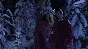 Junger nette Mann und die Frau, die in den roten Kostümen gekleidet wird, bewegen sich in Wald des verschneiten Winters stock video footage