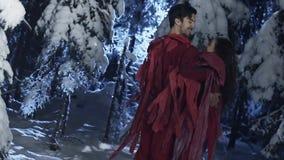 Junger nette Mann und die Frau, die in den roten Kostümen gekleidet wird, tanzen in Wald des verschneiten Winters stock video