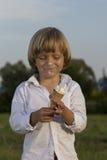 Junger netter blonder Junge, der eine geschmackvolle Eiscreme isst Stockbild