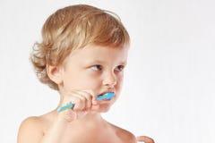 Junger netter blonder Junge, der seine Zähne putzt Lizenzfreie Stockfotografie