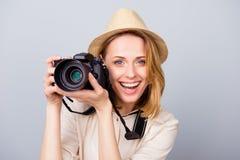 Junger netter blonder weiblicher Fotograf lächelt auf dem Licht Lizenzfreie Stockfotografie