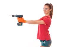 Junger netter Brunettefrauenerbauer in der Uniform mit Gläsern und bohren herein ihre Hände machen reovations lokalisiert auf Wei stockbild