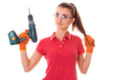 Junger netter Brunettefrauenerbauer in der Uniform mit Gläsern und bohren herein ihre Hände machen reovations lokalisiert auf Wei stockfoto
