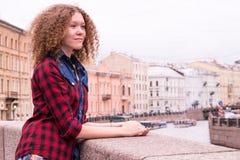 Junger netter gelockter träumerischer Jugendlicher, der auf dem Moika-Damm in St Petersburg steht lizenzfreies stockfoto