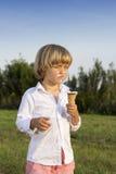 Junger netter Junge, der eine geschmackvolle Eiscreme isst Lizenzfreie Stockbilder