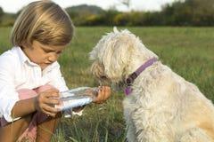 Junger netter Junge, der seinem Hund Wasser gibt Stockfotografie