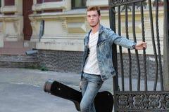 Junger netter Kerl mit dem roten Haar am Tor mit einer Gitarre im Fall stockfotografie