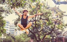 Junger netter Mann, der in den Park springt Lizenzfreies Stockfoto