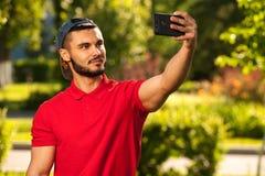 Junger netter Mann, der selfie Bild im Park macht Stockfotografie