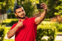 Junger netter Mann, der selfie Bild im Park macht Lizenzfreie Stockfotografie