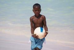 Junger netter schwarzer Junge in den blauen kurzen Hosen, die Fußball auf dem sonnigen karibischen Strand spielen Bavaro-Strand, lizenzfreies stockfoto