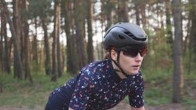 Junger netter weiblicher Radfahrer, der auf Fahrrad aus dem Sattel heraus sprintet fokussiertes Gesicht Radfahrentraining stock video footage