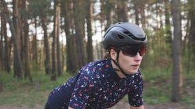 Junger netter weiblicher Radfahrer, der auf Fahrrad aus dem Sattel heraus sprintet fokussiertes Gesicht Radfahrentraining Langsam stock footage