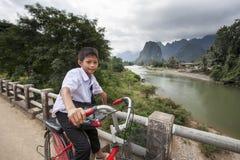 Junger nicht identifizierter Junge, der zurück von der Schule auf einer Holzbrücke radfährt Lizenzfreies Stockfoto