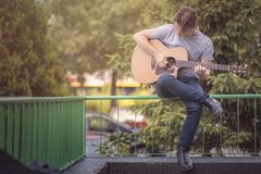 Junger nobler Mann, der eine Gitarre in einem Vorstadtgebiet im Freien spielt lizenzfreies stockfoto