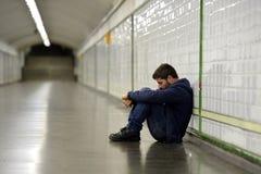 Junger obdachloser Mann verlor in der Krise, die auf Boden Straßen-U-Bahntunnel sitzt Lizenzfreies Stockfoto