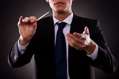 Junger Orchesterleiter, der mit seinem Taktstock verweist Lizenzfreie Stockfotografie