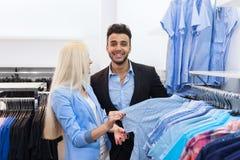 Junger Paar-Mode-Shop, glücklicher lächelnder Mann und Kundinnen, die das Einkaufen der Kleidungs-formellen Kleidung wählen Lizenzfreies Stockfoto