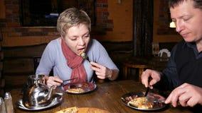 Junger Paarmann und -frau, die Pizza in einem Café isst stock video footage
