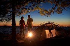 Junger Paarmann und -frau, die Rest am touristischen Zelt und an brennendem Lagerfeuer auf Seeufer nahe Wald hat stockbilder