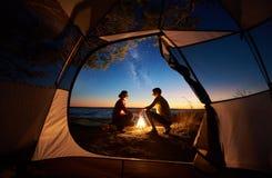 Junger Paarmann und -frau, die Rest am touristischen Zelt und an brennendem Lagerfeuer auf Seeufer nahe Wald hat stockbild