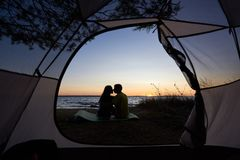 Junger Paarmann und -frau, die Rest am touristischen Zelt und an brennendem Lagerfeuer auf Seeufer nahe Wald hat stockfotografie