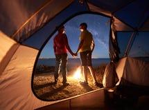 Junger Paarmann und -frau, die Rest am touristischen Zelt und an brennendem Lagerfeuer auf Seeufer nahe Wald hat lizenzfreies stockfoto