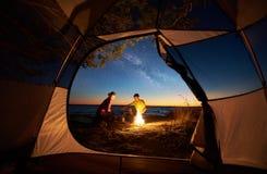 Junger Paarmann und -frau, die Rest am touristischen Zelt und an brennendem Lagerfeuer auf Seeufer nahe Wald hat lizenzfreies stockbild