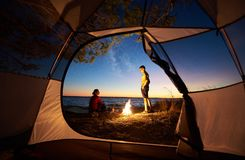 Junger Paarmann und -frau, die Rest am touristischen Zelt und an brennendem Lagerfeuer auf Seeufer nahe Wald hat stockfoto