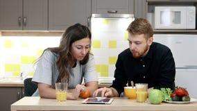 Junger Paarmann und -frau mit Tablette das Frühstück essend, das zu Hause durch Tabelle in der Küche sitzt stock footage