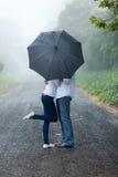 Junger Paarregenschirm stockbild