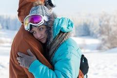Junger Paarskischutzbrillenumarmungs-Winterschnee Lizenzfreies Stockfoto